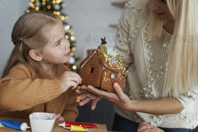 Daughter and mother decorating gingerbread house