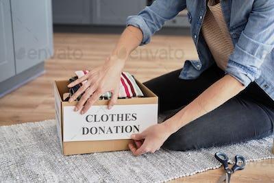 Woman  preparing box for clothes donation