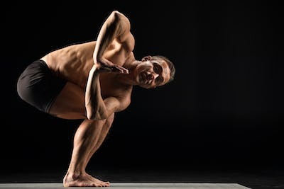 Athletic man practicing yoga with palms together performing Twisted chair pose and looking at camera
