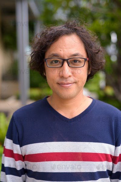 Face of Japanese man with curly hair wearing eyeglasses in the rooftop garden