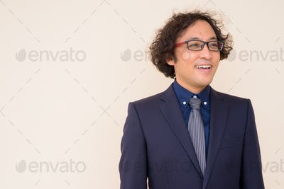 Portrait of happy Japanese businessman with curly hair thinking