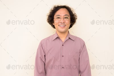 Portrait of happy Japanese businessman with curly hair smiling