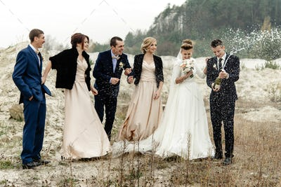 bride and groom with happy groomsmen and bridesmaids having fun and laughing and popping champagne