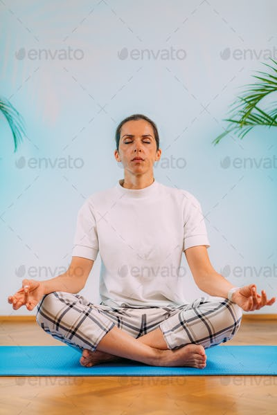 Relaxed Woman Meditating at Home. Measuring HR with Smart Watch.