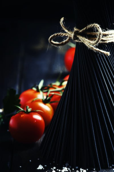 Spaghetti and tomatoes, still life in low key, selective focus