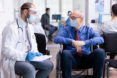 Doctor consulting disabled senior man
