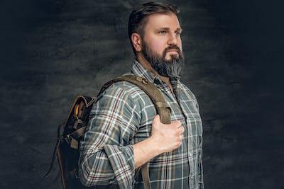 A man holds backpack on his shoulder.