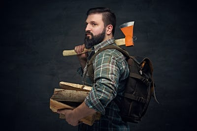 Bearded middle age male holds an axe and firewoods.
