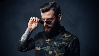 Portrait of bearded tattooed hipster male dressed in a military jacket.