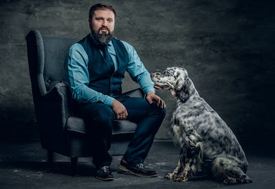 Stylish bearded male sits on a chair and the Irish setter dog.