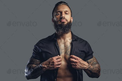 Tattooed bearded male taking off his shirt.