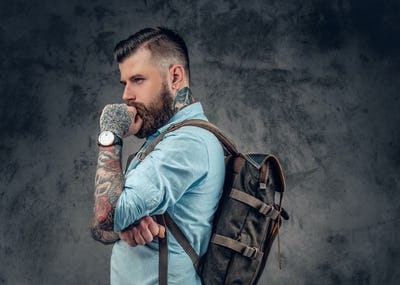 bearded male with tattoos on his arms holds urban backpack.