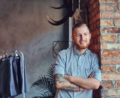 Portrait of a bearded modern male with tattoos on his arms.
