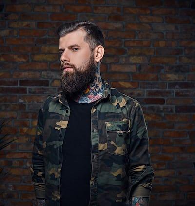 Tattooed bearded male in military jacket.