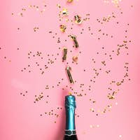 Green champagne bottle and streamers flow on pink
