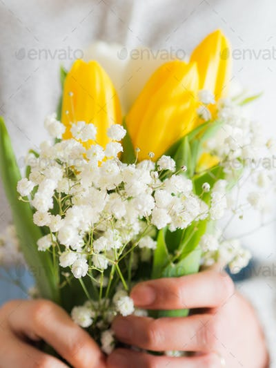 Woman holding bouquet of tulips. Woman's day