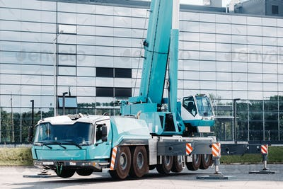 A large blue truck crane stands ready to operate on hydraulic supports on a platform next to a large