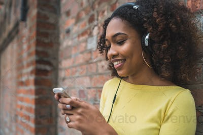 Afro-American woman with mobile phone and headphones
