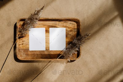Top view of two blank paper sheet cards on a wooden tray with dry grass