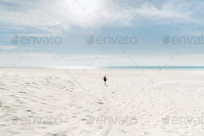 a child runs along a white beach to the Baltic sea in Sunny weather.A little girl runs across the