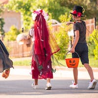 Back view of three friendly children in halloween costumes carrying sweet treats