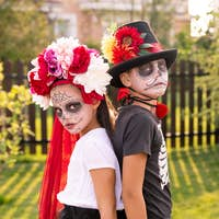 Gloomy halloween boy and girl with painted faces standing close to one another