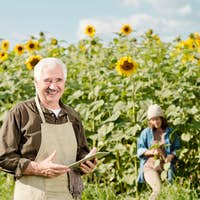 Mature cheerful male farmer in workwear using touchpad in front of camera