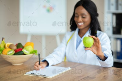 Cheerful African American nutrition adviser planning meals for client at clinic, copy space