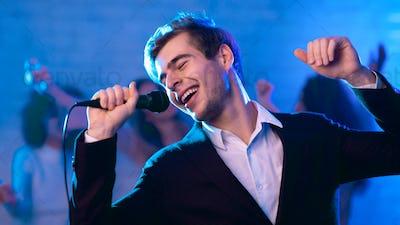Young Man Singing Song Having Fun Partying At Night Club