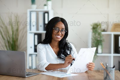Beautuful black business lady working with documents at desk in office