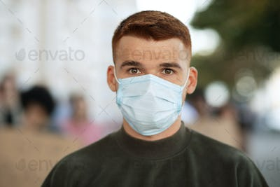 Guy in face mask over group of demonstrators