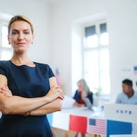 Portrait of confident woman voter in polling place, usa elections concept