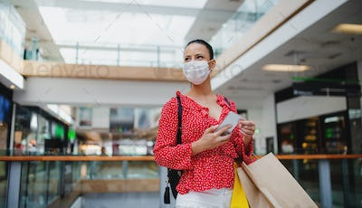 Woman with face mask standing with smartphone indoors in shopping center, coronavirus concept