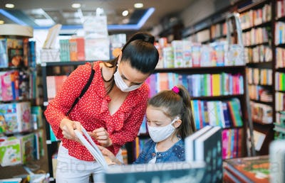 Mother and daughter with face mask shopping in bookshop, coronavirus concept