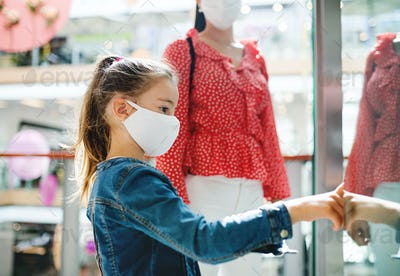 Mother and daughter with face mask indoors in shopping center, coronavirus concept