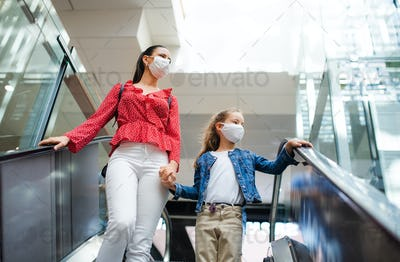 Mother and daughter with face mask on escalator indoors in shopping center, coronavirus concept