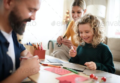 Family with small daughter indoors at home at Christmas, making Christmas cards