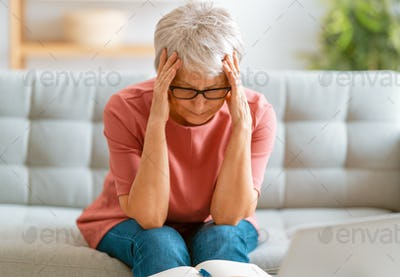 Senior exhausted woman having headache