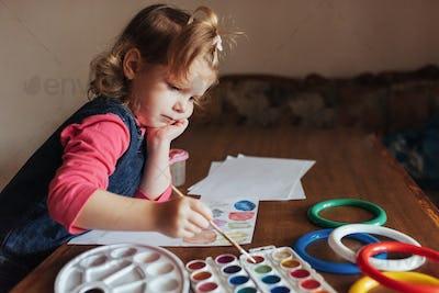 Cute happy little girl, adorable preschooler, painting with wate