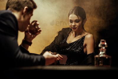 Man in suit drinking whisky while playing poker with beautiful young woman