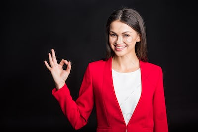 Young attractive businesswoman showing ok gesture and smiling at camera isolated on black