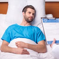 Doctor bringing medical document to male patient lying in hospital bed