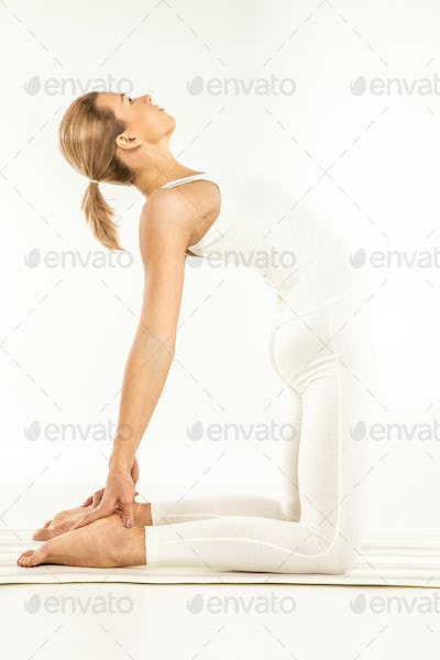 Woman practicing yoga standing in Ushtrasana position or Camel pose  isolated on white