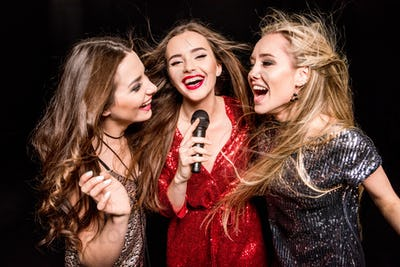 Three gorgeous young women in festive dresses singing karaoke isolated on black