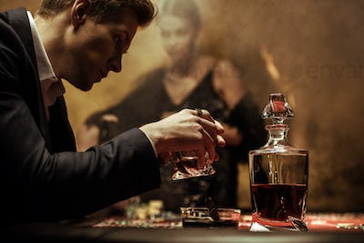 Profile portrait of serious young man in suit drinking whisky in casino