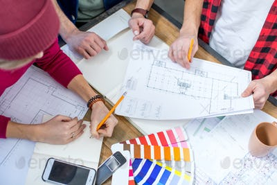 Close-up partial view of male and female designers working at project with blueprints