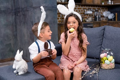 Little boy and girl in bunny ears sitting on sofa and eating sweets