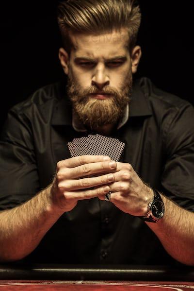Serious bearded man holding poker cards on black