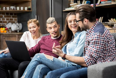 Friends using laptop while sitting on sofa in living room