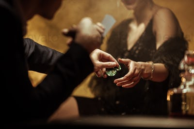 Partial view of elegant couple playing poker and sharing casino chips